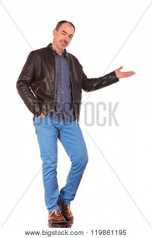 attractive mature man in leather jacket presenting standing with one hand in pocket while smiling at the camera in isolated studio background