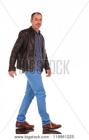confident casual mature man in leather jacket walking in isolated studio background while looking at the camera