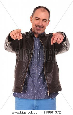 mature elegant man in leather jacket standing and pointing with both hands to the camera while smiling in isolated studio background