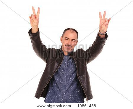 mature casual man in leather jacket showing the victory sign with both hands while looking at the camera in isolated studio background