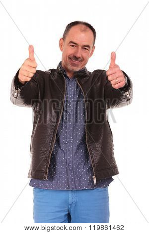 mature man in leather jacket posing standing in isolated studio background showing the victory sign with both hands while looking at the camera