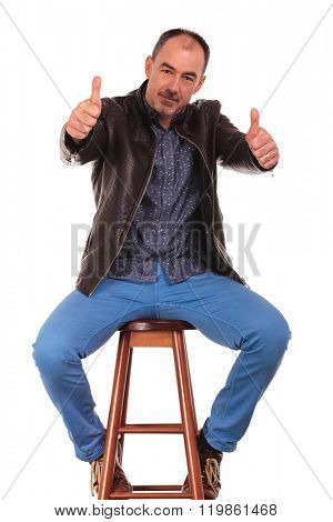 mature man posing seated with legs wide open in isolated studio background while showing thumbs up with both hands