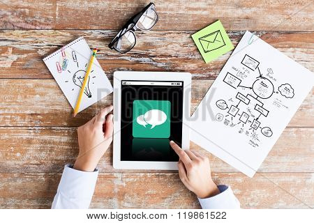 business, education, people and technology concept - close up of female hands pointing finger to tablet pc computer with messenger icon on screen, scheme and eyeglasses