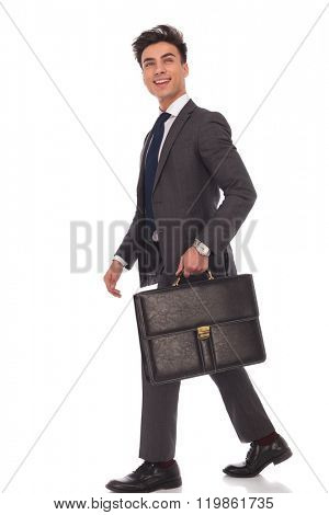 side view of a walking business man with briefcase looking up and laughing on white background