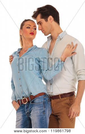 attractive couple posing looking away from the camera in isolated studio background. he embraces her from behind while she turns at him with hand in pocket.