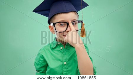 childhood, school, education, knowledge and people concept - happy boy in bachelor hat or mortarboard and eyeglasses over green school chalk board background