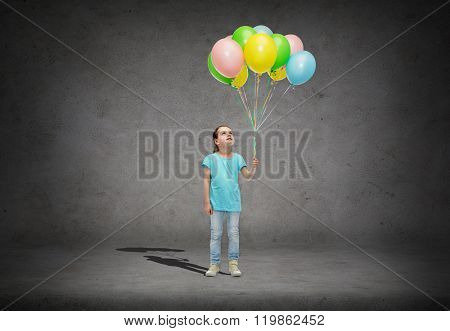 childhood, fashion, imagination and people concept - happy little girl looking up and holding bunch of colorful helium balloons on strand over concrete room background