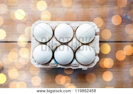easter, food, cooking and object concept - close up of white eggs in egg box or carton wooden surface