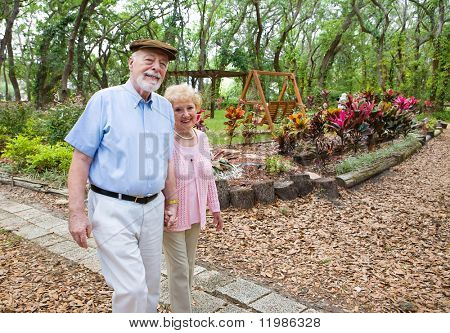 Happy senior couple taking an afternoon stroll in the park.