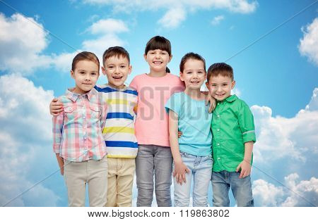 childhood, fashion, friendship and people concept - group of happy smiling little children hugging over blue sky and clouds background