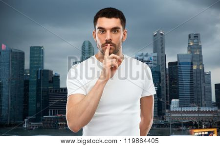 silence, gesture and people concept - young man making hush sign over evening singapore city background