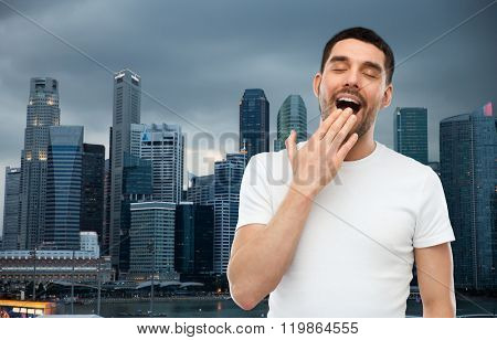 rest, bedtime and people concept - tired yawning man over evening singapore city background