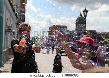 The Girl Starts Up Soap Bubbles On The Background Of The Main City Sights - Kazan Cathedral. Summer