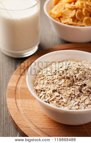 Oatmeal And Cornflakes In White Bowls On Wooden Board