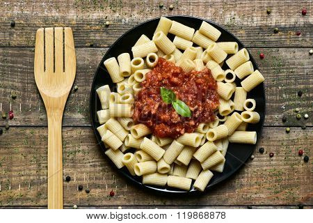 high angle shot of a wooden fork and a black plate with penne rigate with bolognese sauce on a rustic wooden table