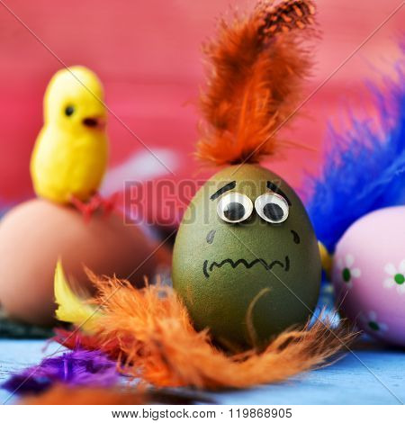closeup of an easter egg ornamented with three-dimensional eyes and a drawn mouth, with a scared face, surrounded by feathers, more easter eggs and a toy chick