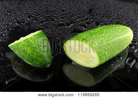 Divided Country Cucumber With Water On Black Background