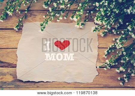 I Love Mom And Happy Mothers Day On Brown Paper With White Flower On Wooden Board