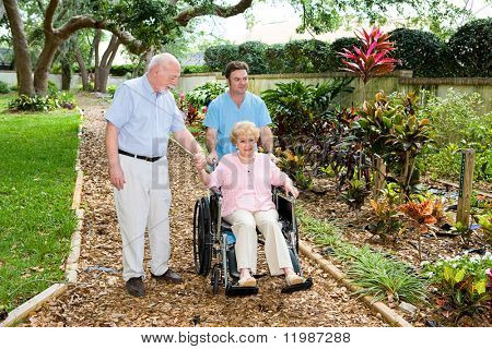 Senior woman in a wheelchair being walked through the nursing home garden by an orderly and her husband.