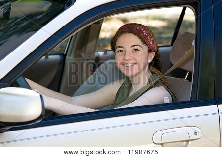 Pretty teen driver smiling behind the wheel of her new car.