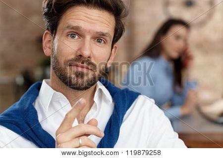 Wondering businessman looking at camera.