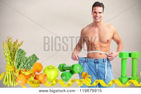 Man measuring waist size over gray background.