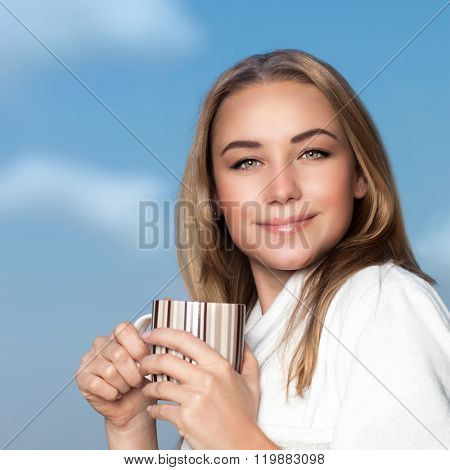 Portrait of pretty woman having morning coffee, wearing bathrobe and standing with mug in hands on the balcony over blue sky background, spending weekend in the hotel