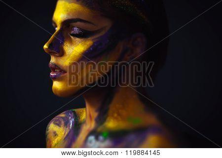 Woman's profile body art against black background
