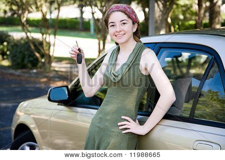 Pretty teen girl leaning on her new car and holding car keys.