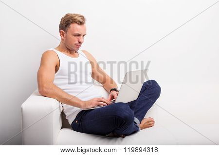 Man sitting on the couch with computer in his lap and browsing internet