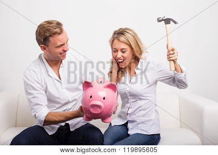 Couple smashing piggy bank with hammer