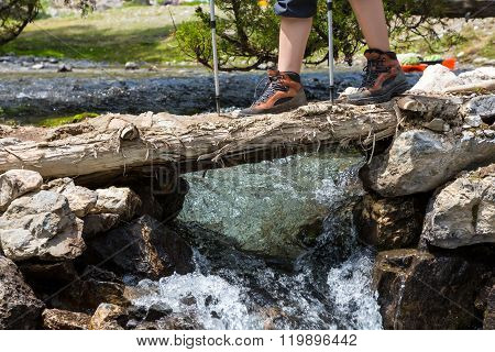 Feet of female hiker on bridge