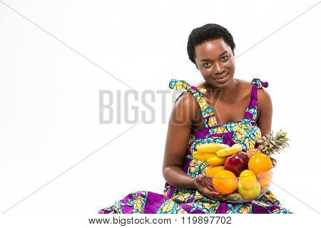 Attractive smiling african american young woman in colorful sundress holding exotic fruits over white background