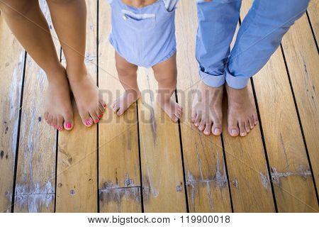 Baby firsts steps holding his parents hands
