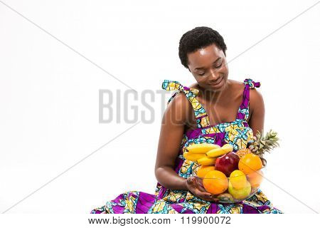 Pretty happy african american young woman in bright sundress sitting and looking at fresh exotic fruits over white background