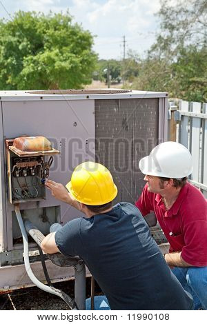 Two AC technicians on a roof repairing an industrial compressor unit.
