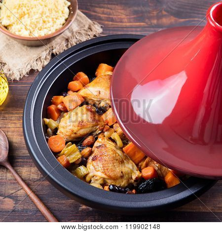 Tagine with cooked chicken and vegetables Wooden background Copy space