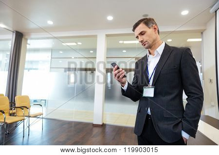 Pensive handsome business man standing in the office and using cell phone