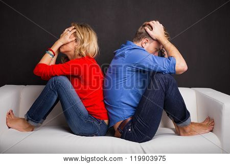 Couple with their backs turned to each other sitting on couch