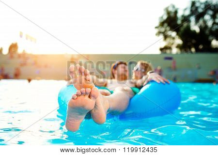 Couple in inflatable ring in pool. Summer and water.