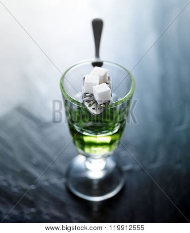 absinthe in pontarlier glass with spoon and sugar cubes