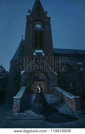 Mysterious woman in black dress near chirch