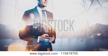 Photo of  businessman holding smartphone. Double exposure, city on the background. Wide