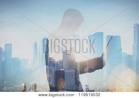Photo of man working with laptop. Generic design laptop holding in his hands. Double exposure backgr
