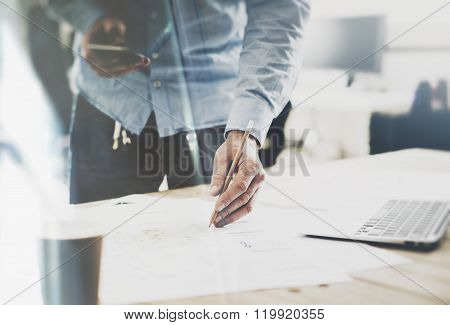 Working process. Businessman holding pencil hands, working at the wood table with new project. Gener