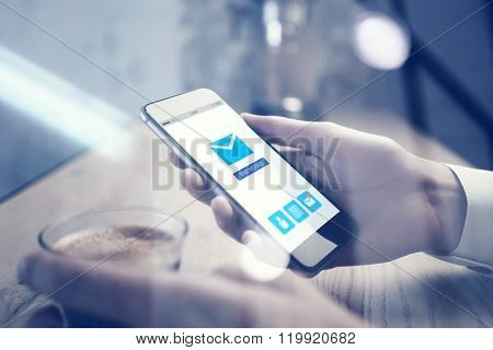 Close up of smartphone holding in female hand. Email app interface screen. Cup espresso on the table