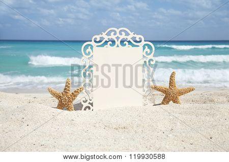 Starfish Holding A Fancy Frame On Ocean Beach