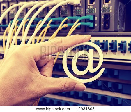 Hand holding email symbol over Network switch and ethernet cables,Data Center Concept.