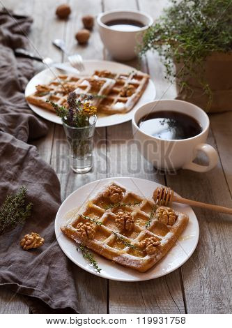 Belgian waffles breakfast with nuts, honey, herbs and coffee.