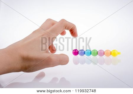 Hand frightning color beads with facial expression on white background